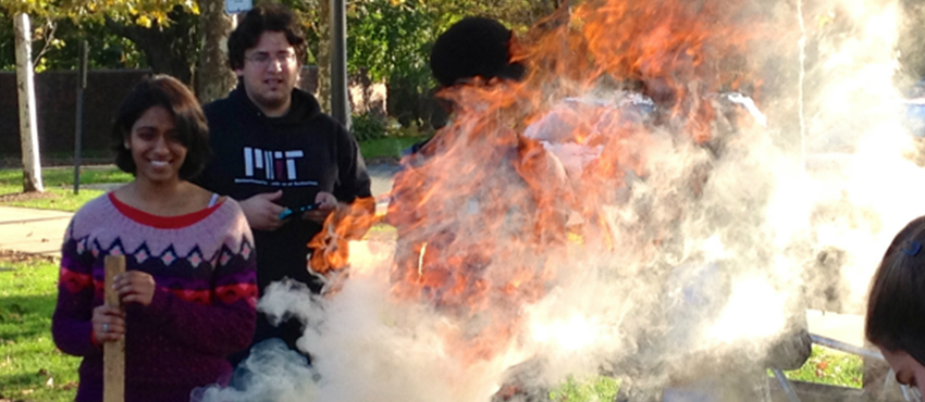 D-Lab students make charcoal from agricultural waste at the MIT Kresge Barbecue Pits.