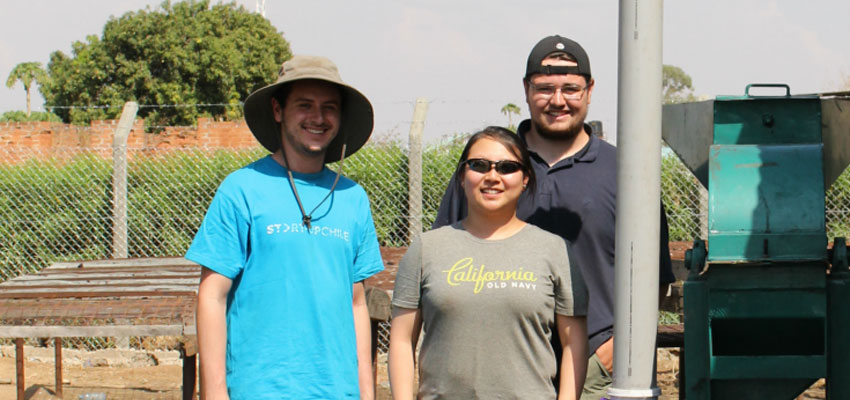 Left to right: Drew Beller '18, Joy Lee '13, and Tim Mangenello '17 stand proudly by a completed charcoal grinder. Photo: Lauren Bustamante