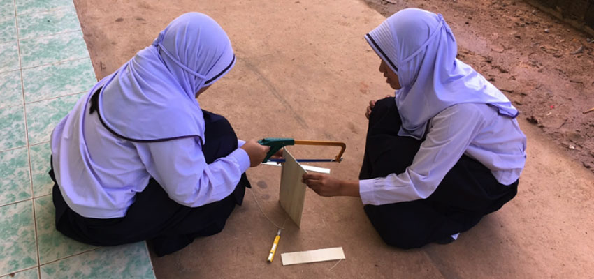 Two students sawing outside to build their prototype in Ao Kapor.
