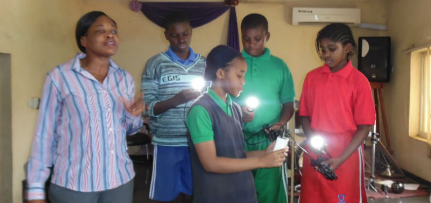Angela Amaka Onah (left) giving a solar lantern demonstartion at a local school (Nigeria).