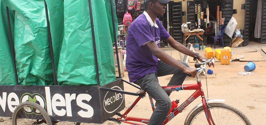 An employee rides one of the Wecyclers' cargo bikes. The startup employs locals to ride door-to-door across the slums of Lagos, Nigeria, to collect recyclables.