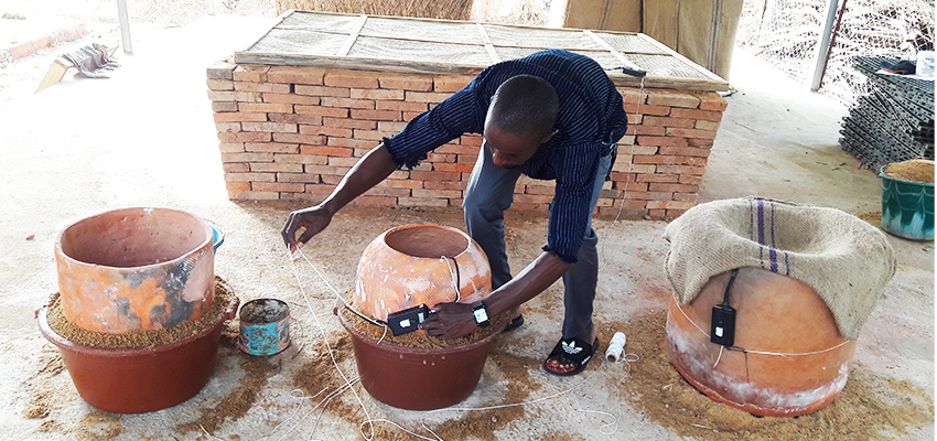 Attaching a sensor to a pot-in-pot evaporative cooler in Bamako, Mali. Photo: Ousmane Sanogo