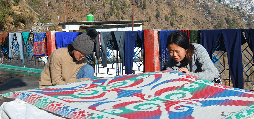 Jackie Lin '19 and Ting Li '20 sewing chatai mats, with foam in between. Nepal, January 2019.