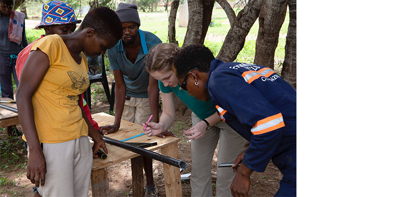 Amelia Seabold 2022 (2nd from right) takes careful measurements with   Maikano Poniso (yellow shirt) and Nyambe Namate (overalls).