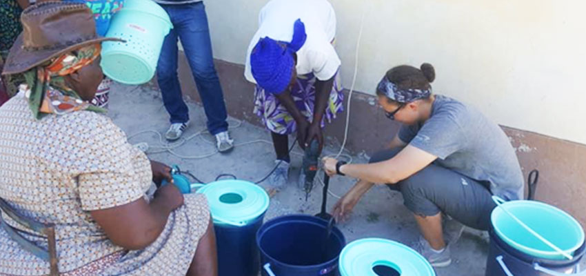 D-Lab student Sloan helps teach local women how to use power drills to create holes in a plunger