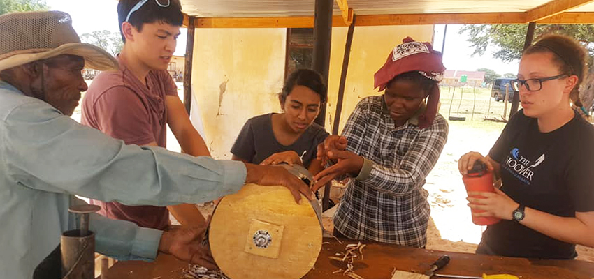 D-Lab Students Sloan and Bhattacharjee along with some of the community members working on the bean thresher.