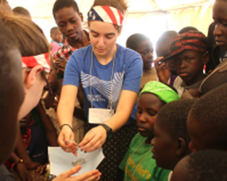Rachel helps students measure the strength of their spaghetti marshmallow tower. (Photo: Nai Kalema)