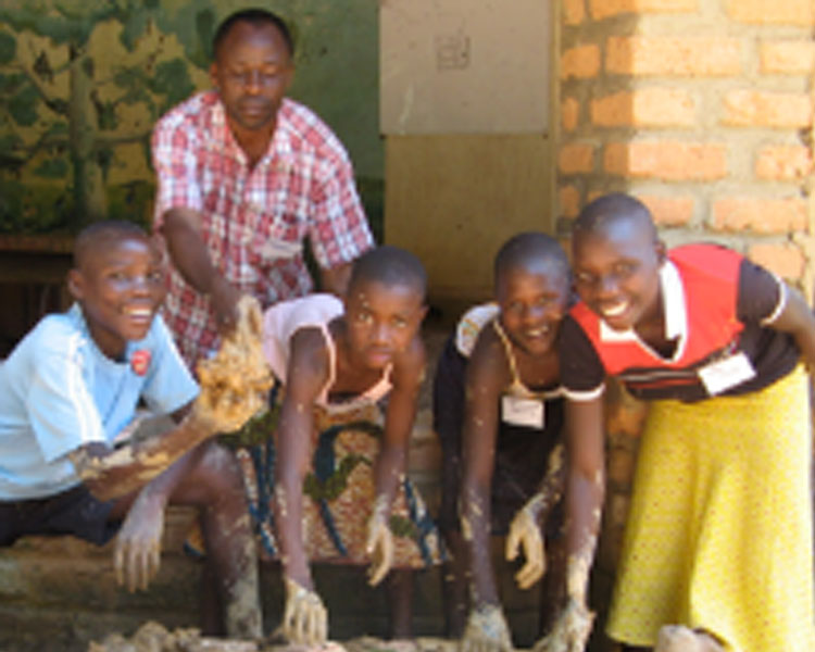Youth building a stove in Kasiisi, Uganda.