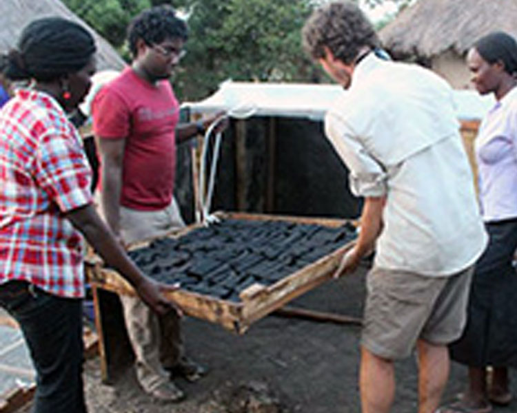 Betty tests a solar dryer for charcoal bricks with her team in Uganda.