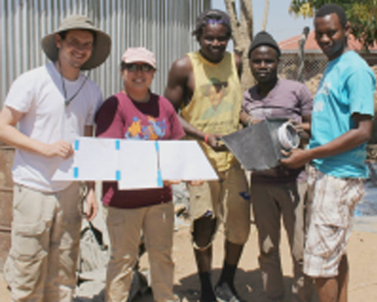 Drew, Joy (EWB), Mambo (AEST), Abudalla (AEST), and Juma (AEST) show off the sketch model and final product of the chute for the charcoal grinder. (Photo: Lauren Bustamante)