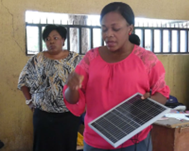 Describing how a solar panel works to local school students (Nigeria).