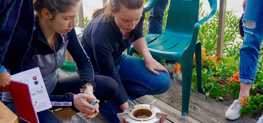 Team members Cayanne and Natalia carrying out tests on the Mimi Moto cookstove with the help of Richard Grinnell - Regional Director of Global Alliance for Clean Cookstoves.