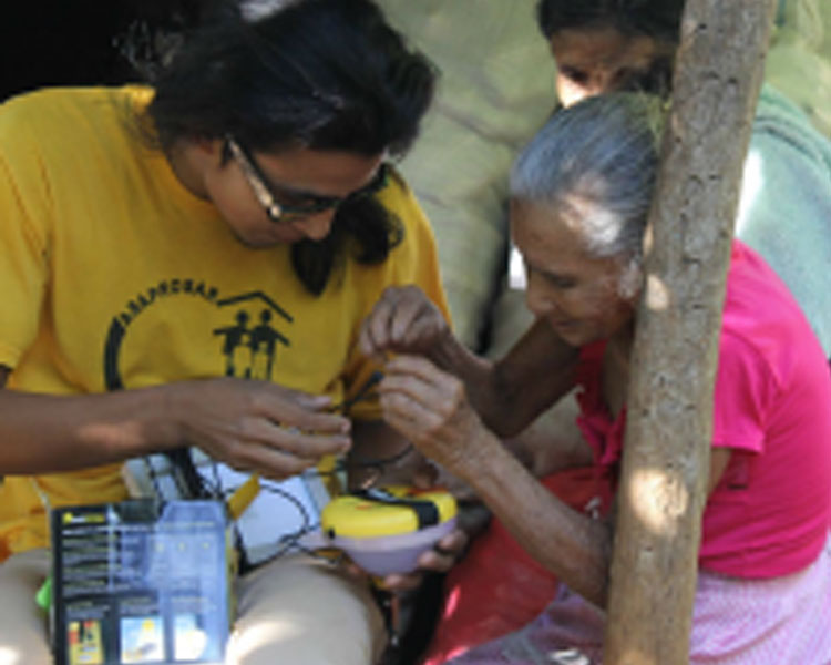 ASAPROSAR staff Geovany Moreno demonstrating a solar lantern to resident of El Sauce.