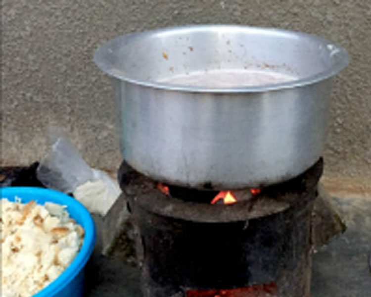 Cookstove in use with bread cubes at the side.