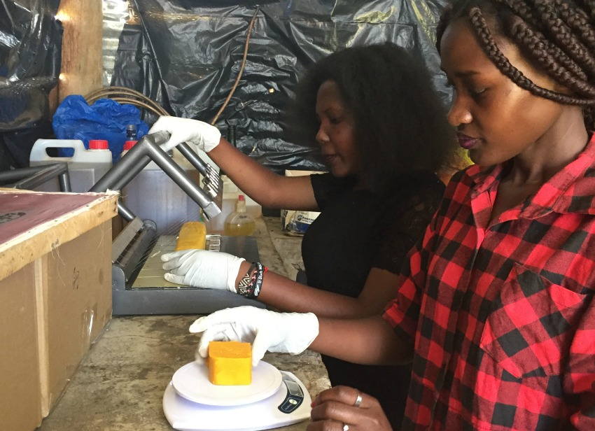 Joan Nalubega (back) and Monica Nantongo are putting the final touches on a batch of their mosquito-repellent soap. Joan's company, Uganics, has tested their product in Germany. The company sells to individuals as well as businesses, such as hotels.