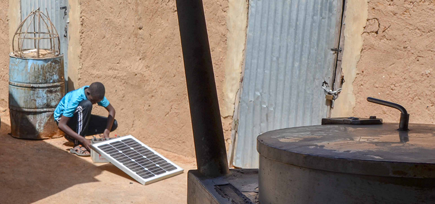 Young man with solar panel, Mali.