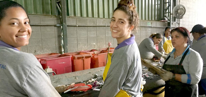 Jessica (left) and Peña (right) showing Talia how to sort recyclable materials at the Jacareí Recicla cooperative in Jacareí, São Paulo.