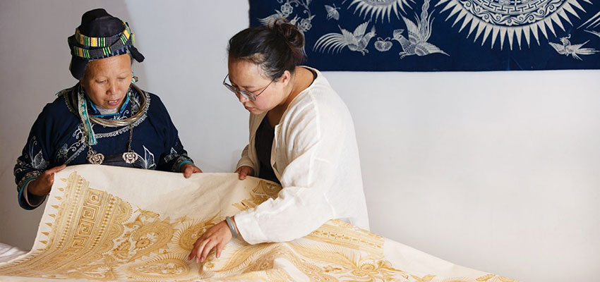 Xiao Liu, right, a community organizer with Roots Studio, looks over a print with an artist from Guizhou, China. Photo: 心奕