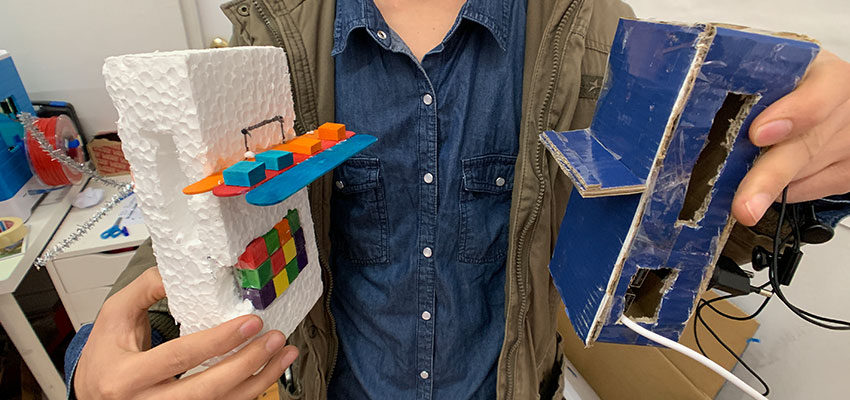 A student holding the sketch models he created to demonstrate his ideas for a power bank case.