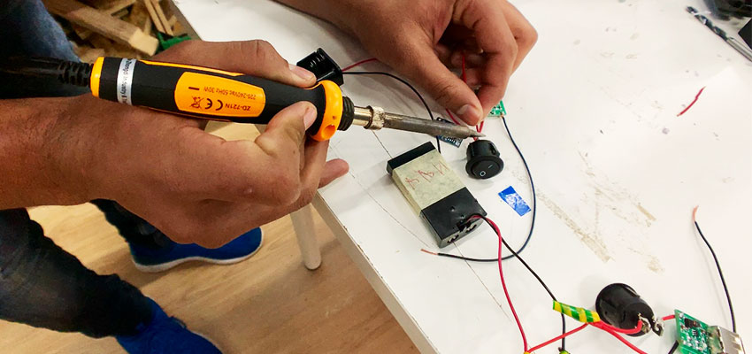 A student solders two wires together to make the circuit for his power bank.