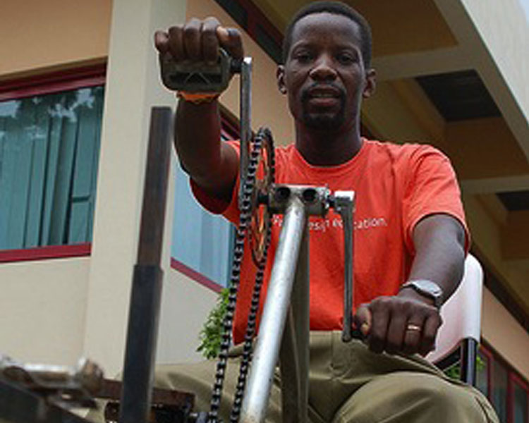 Bernard demonstrating his pedal-powered hacksaw at Maker Faire Africa in Ghana. Photo Credit: Erik Hersman