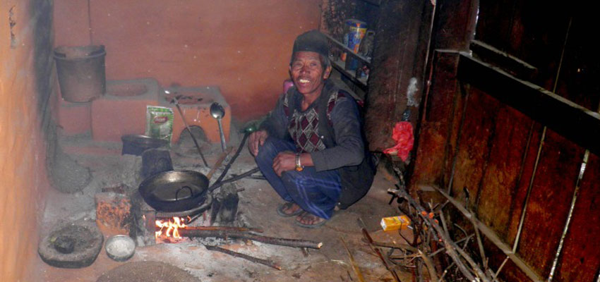 A resident from Salambu cooking food using forest wood.