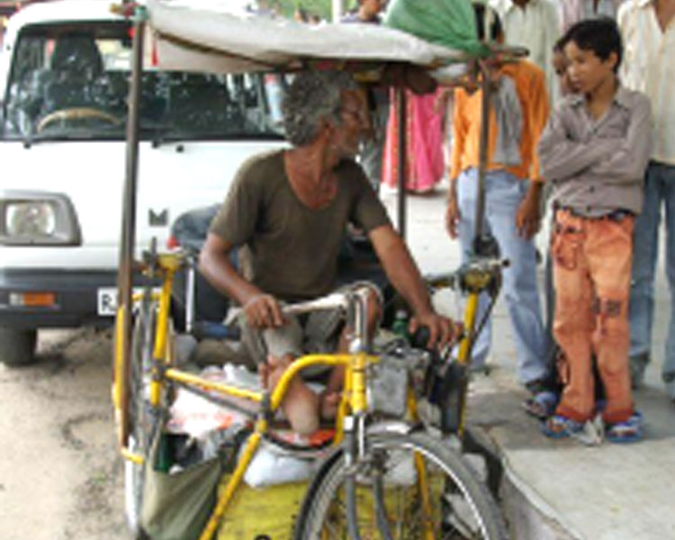 A polio survivor in Jaipur, India uses a handcycle for mobility and income generation.