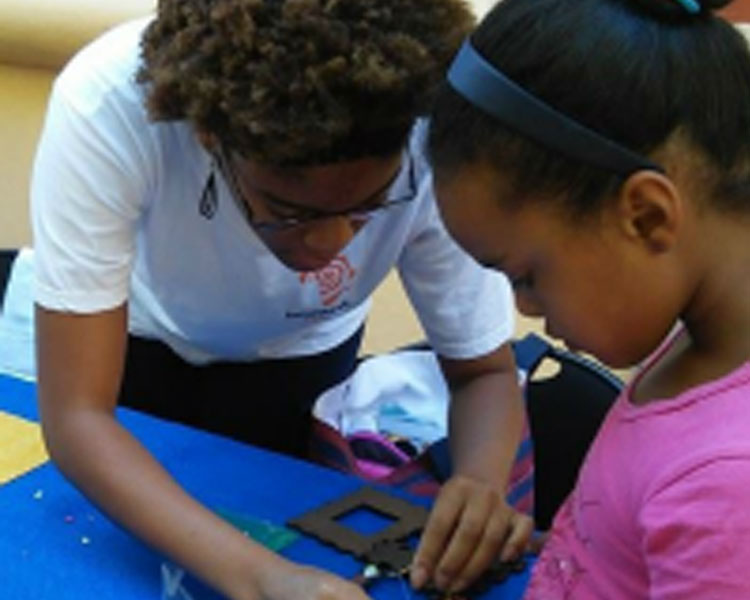 Netia assisting a young participant in assembling her Solar USB Charger at a Mbadika Workshop in Cape Town, South Africa.