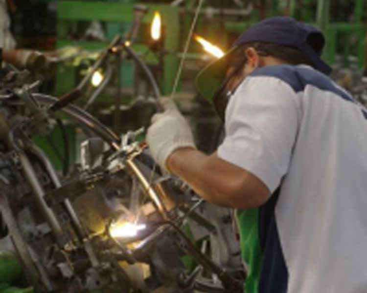 A worker in Jakarta, Indonesia mass-produces low-cost rugged offroad wheelchairs for bulk purchase by an international humanitarian organization