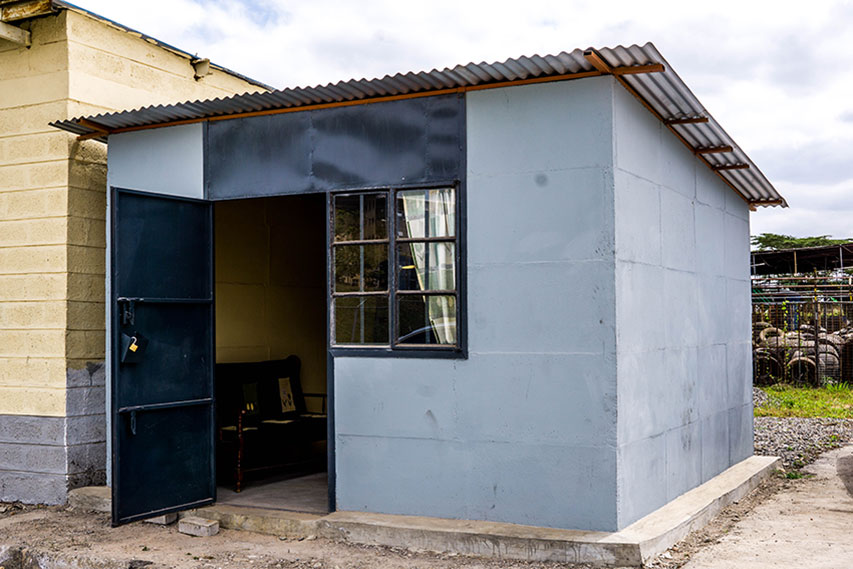 Kwangu Kwako Limited's 12'x12' show house, demonstrating its secure metal door and sturdy modular concrete design