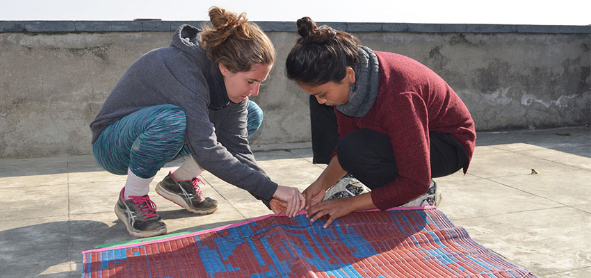 Ines and Sandhya working together to sew two chatai mats together on the roof of the Solambu Hospital Center.